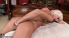 White Angel fists herself in knee high black boots over edge of bed