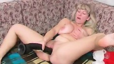 Busty blonde Mila K pulls out her huge black dildo and shoves it in