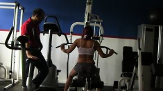 Trainer helps a hottie work out on the equipment before he nails her