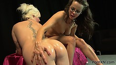 Brunette gets soaked with oil and fist-fucked by a horny blonde