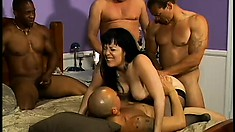 There are four guys in the bedroom and they all want to fuck this busty brunette