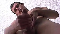 Young stud with a huge cock strokes himself off for the camera