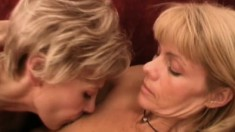 Two luscious mature blondes indulging in lesbian action on the couch